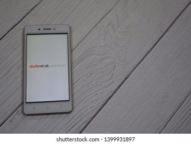 SUBANG, SELANGOR - 16 MAY 2019 - Shutterstock Contributor appplication on a phone with selective focus. White wooden background. Shutterstock is a famous platform to buy and sell media worldwide.