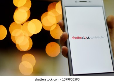 SUBANG, SELANGOR - 16 MAY 2019 - Hand is holding a phone with Shutterstock Contributor application is loading. Light bokeh background.