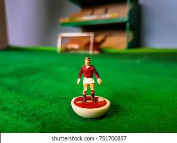 Subbuteo football figure lined up on a grass football field, Manchester Utd, Arsenal, Liverpool