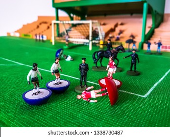Subbuteo football figures in action in front of the goal on a grass field, Arsenal v Tottenham Hotspur with police and horses