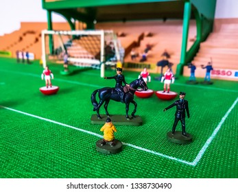 Subbuteo football figures in action in front of the goal on a grass field, with police and horses