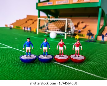 Subbuteo football figures lined up in front of the goal on a grass field, Arsenal, Chelsea, Everton