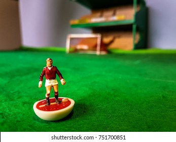 Subbuteo football figures lined up on a grass football field, Manchester Utd, Arsenal, Liverpool