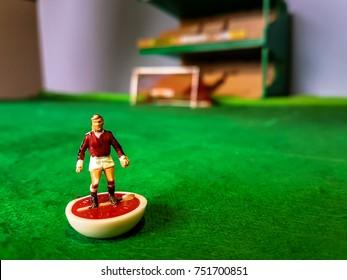 Subbuteo football figures lined up on a grass football field, Manchester Utd, Arsenal, Liverpool