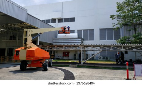 Subcontractor is working on a high place with a boom lift, Roof is installed to keep the hot sun in summer, Dangerous work on high places, High risk hazardous work using a boom lift, High work.