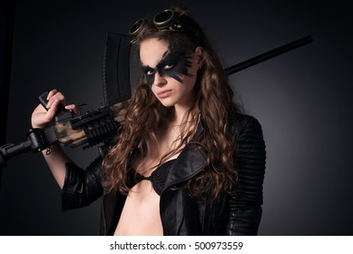 Subculture, fantasy concept. Portrait of wild, tough girl holding metal weapon over dark gray background. Crow wing mask make-up. Rock, vintage, retro-futurism style. Studio shot