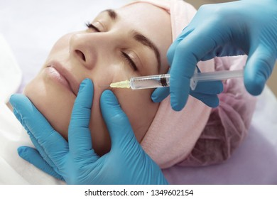 Subcutaneous injection into girl's face. Doctor cosmetologist doing pull-injection in face model. Syringe, face, needle, lift - the concept of rejuvenation. Tightening of skin of the face.