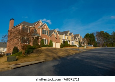 Subdivision view. Brick two-storey cottages on the street at the city suburb. Two-storey houses on the street, blue sky. Alpharetta, GA, USA