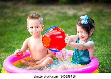 Subject childhood summer games in the yard. Caucasian brother and sister playing plastic toys bucket sitting in the water, inflatable round children's pool. Summer is hot, rest in swimsuits.