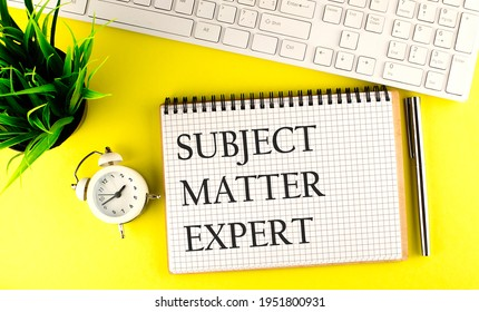 Subject Matter Expert text on notebook with keyboard , pen and alarm clock on yellow background