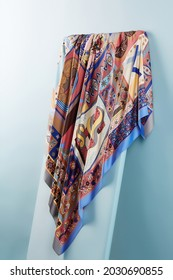 Subject photo of bright scarf with colorful ethnic design. Stylish silk headkerchief is hanging on the white board.