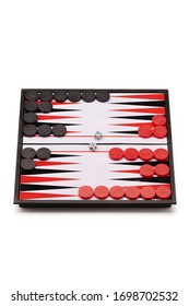 Subject shot of backgammon on the white backdrop. The narde set consists of a folding board, black and red playing chips and two cubes.