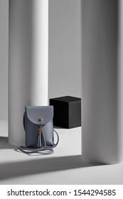 Subject shot of a gray-blue rectangular leather clutch with a long handle, a snap button fastening and leather tassels. The mini bag is isolated in the gray interior with geometric design.