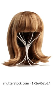Subject shot of a natural looking blonde wig with bangs and twisted strands fixed on the white metal wig holder. The stand with the wig is isolated on a white background.
