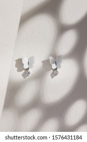 Subject shot of a pair of stud earrings isolated on the beige surface with gray shadows. Each of the earrings is made as white gem butterfly with a sparkling crystal pendant in a silver chase.