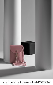 Subject shot of a powder pink rectangular leather clutch with a long handle, a snap button fastening and leather tassels. The mini bag is isolated in the gray interior with geometric design.