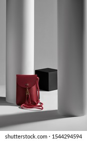 Subject shot of a red rectangular leather clutch with a long handle, a snap button fastening and leather tassels. The mini bag is isolated in the gray interior with geometric design.