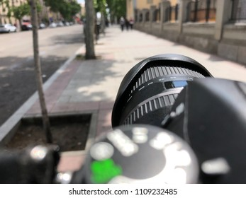 subjective view of the photographer taking pictures in the street. first person view on a camera lens or photographic objective.