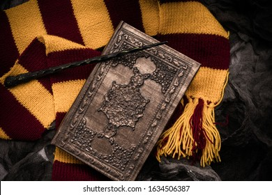 Subjects of the school of magic. Scarf, magic wand, book of spells on grey dark rag background. - Shutterstock ID 1634506387