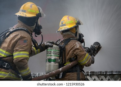 Sublimity, Oregon/USA - 07-13-2011  Close up of two fire fighters spraying water on the house