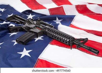 Submachine gun on an American flag with stars and stripes