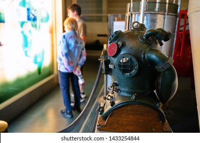 Submarine Force Museum, Groton CT USA, Jun 2019. Grandmother and grandson looking at a map of war tactics among a focused deep sea diving helmet.