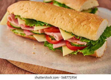 Submarine sandwich with ham, cheese, tomatoes, lettuce, cucumbers and onions on a wooden background