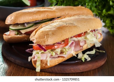 Submarine sandwiches with ham, cheese, tomatoes, cabbage and cucumber. Fresh delicious dish