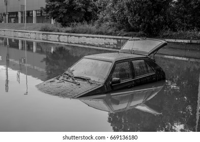 A submerged car, a vehicle that was burnt down due to heavy flooding, occurred after heavy rainfall. Natural disaster.