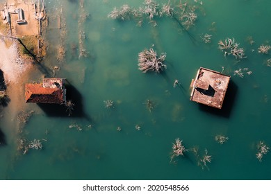 submerged house with tiled roof and dam lake view from above