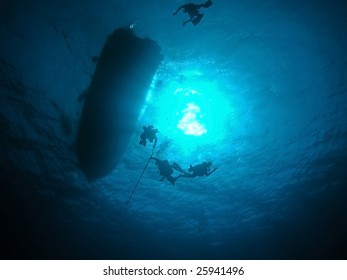 Submerged scuba diver surfacing to anchored boat