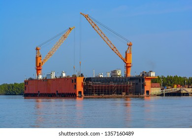 Submersible floating dry dock with dock cranes moored at river bank. Guinea, West Africa.