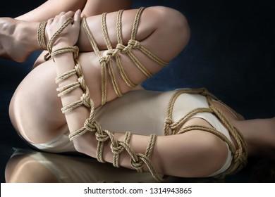 Submission slave woman bound in erotic fashion art style rope shibari kinbaku Japanese bondage knot. Bdsm sadomasochism mistress master dominant fetish punishment flogging sadism masochism concept.