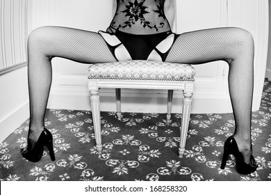 submissive sexy woman playing sexual game sitting on a chair with the legs wide spread wearing high heels hosiery stockings lingerie