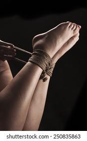 Submissive woman in hog tie bondage position on black background / BDSM theme