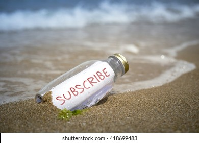 Subscribe written on paper in a bottle washed ashore and layed on the sand