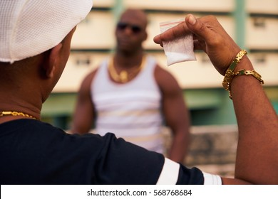 Substance abuse, crime, social issues, drugs. Hispanic and black gang members meeting and fighting over cocaine, heroin and money. Man selling drug dose to junkie.