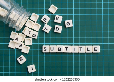 Subtitle word made of square letter block on green square mat background.