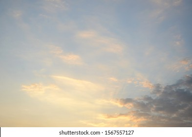 Subtle background of sunset sky and clouds in winter season with golden yellow grey white and blue shades.