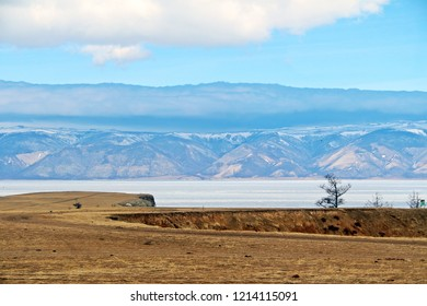 Suburb area on Olkhon island in Baikal lake in winter. Fantastic view like a drawing picture, white blue mountains below the white clouds behind ice lake and the brown golden field