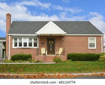 Suburban brick bungalow home autumn leaves blue sky clouds USA