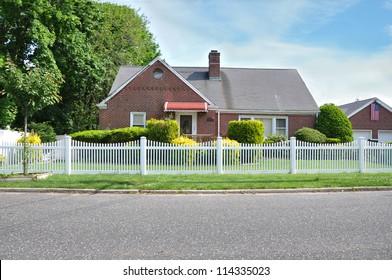 Suburban Brick Home white picket fence American Flag residential neighborhood street