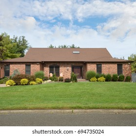 Suburban Brick Ranch home blue sky clouds USA