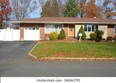 Suburban brick ranch style home white picket fence blacktop driveway autumn blue sky day residential neighborhood USA