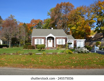 Suburban brown bungalow home autumn day clear blue sky residential neighborhood USA