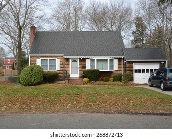 Suburban Brown wood Shingle Cape Cod style home Autumn day residential neighborhood USA