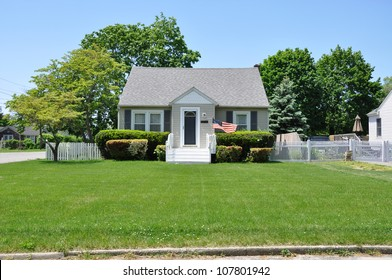 Suburban Bungalow Home American Flag Waving Residential Neighborhood Blue Sky Day