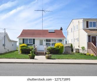 Suburban Bungalow Home with Skylight Window Antenna Blue Sky Clouds