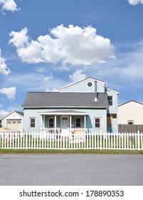 Suburban Bungalow style Home White Picket Fence Residential neighborhood USA Blue Sky Clouds