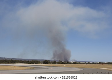 A  suburban bushfire burning on a hot afternoon  near the runways of Perth International Airport, Western Australia  delays take off and landing for many aircraft in early summer.